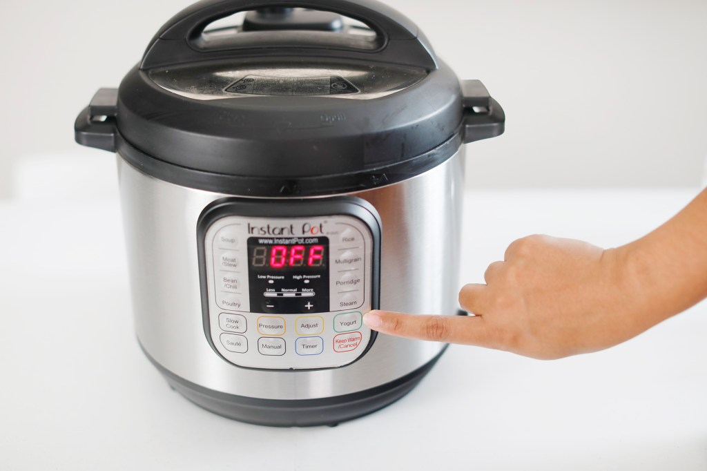 pointing to the yogurt button on instant pot