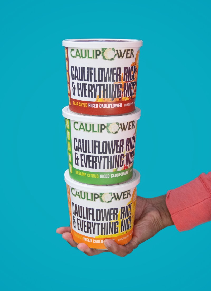 Woman's hand holding three riced Caulipower frozen cups, 3 different flavors with a blue backdrop.
