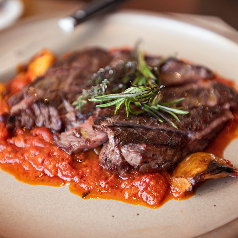 a plate of skirt steak served over confit piquillo pepper, garlic, and roasted tomato