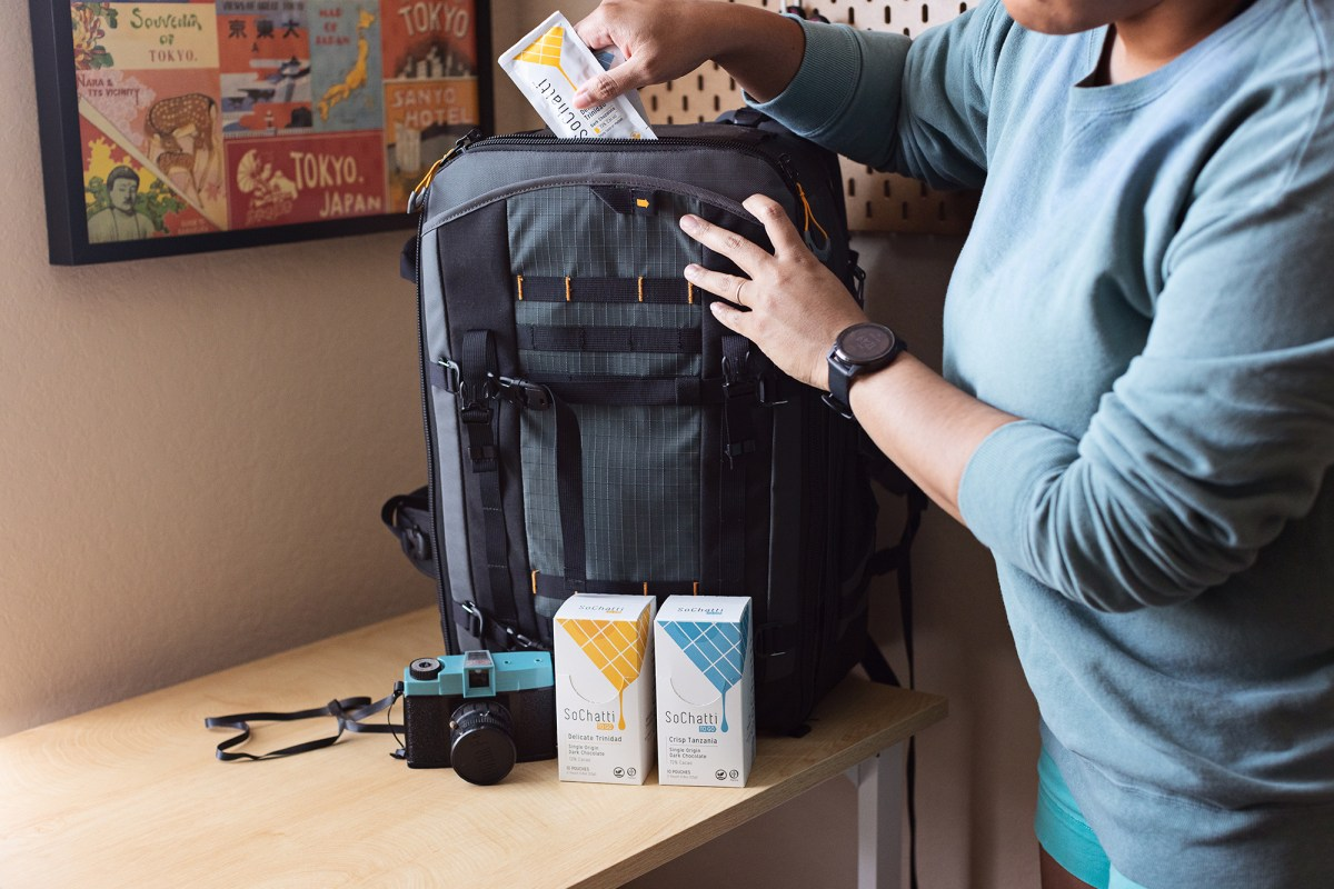 woman packing camera bag with sochatti chocolate pouches. in front of her bag are a blue film camera and sochatti chocolate boxes