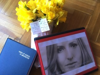 image shows a bunch of yellow flowers, a large blue book with 'voices of kosovo in manchester on the cover and a photograph of a woman, displayed on a table