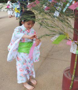 七夕飾りをつるす子供