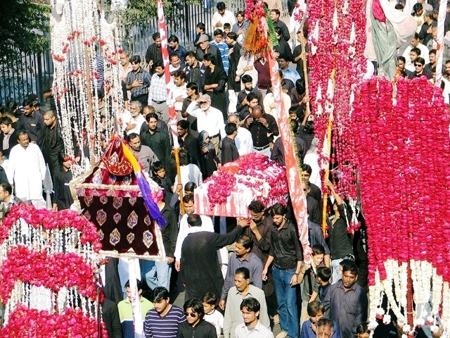 Use of alams in a Pakistani Ashura celebration in Karachi. Similar to Dezfuli processions, some men individually hold an alam as they walk.