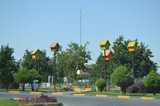 A series of birdhouses on stilts in the middle of a rotary (maidan)