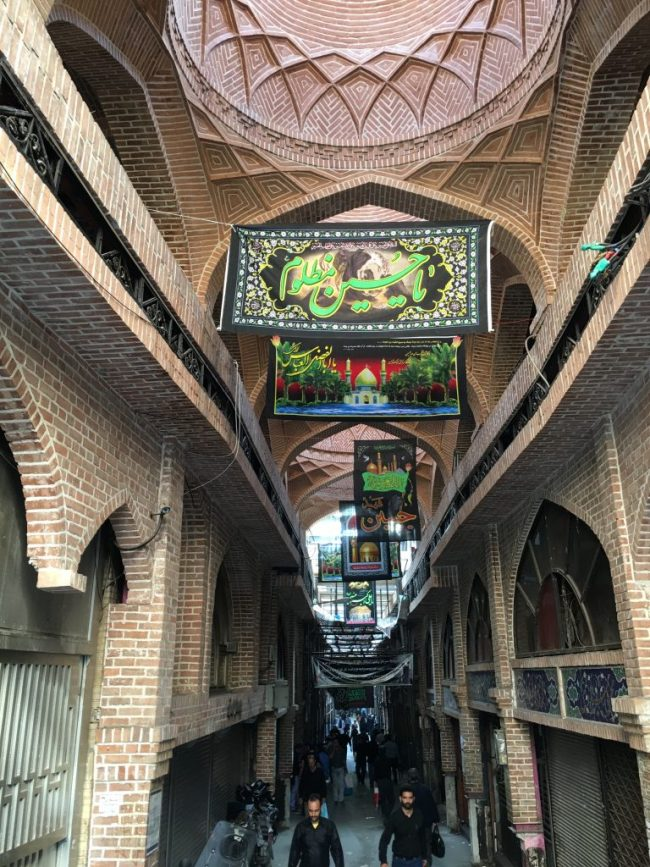 """Tehran's Grand Bazaar, like many other places in Iran, will be decorated with black flags remembering Husayn until Arbaeen, or the """"the 40t,"""" when the mourning period comes to an end."""