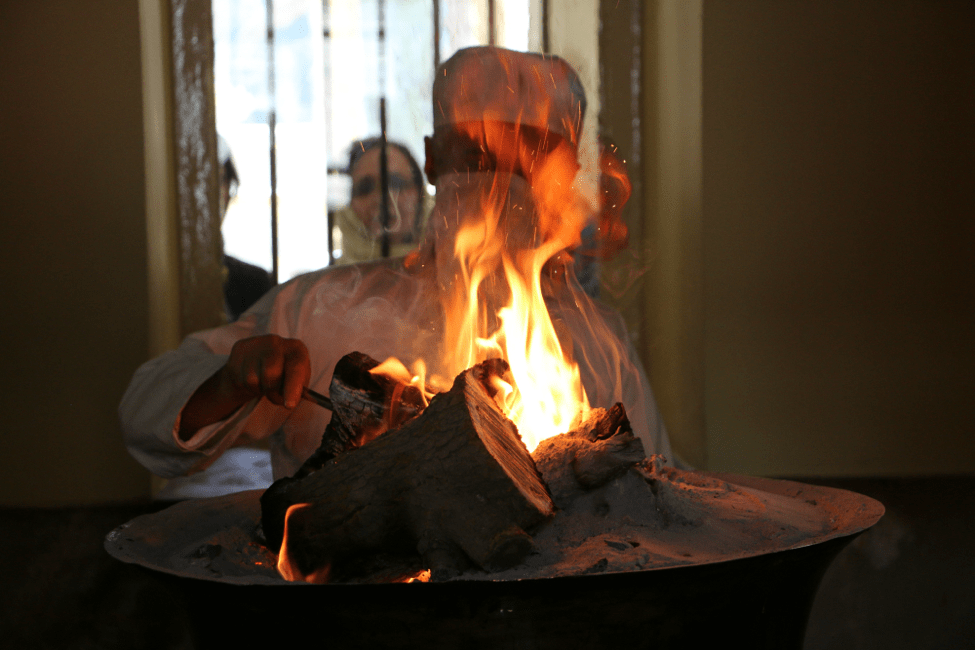 The Mobed puts fresh logs of wood into the fire and continually stokes the flames of the New Year's fire.