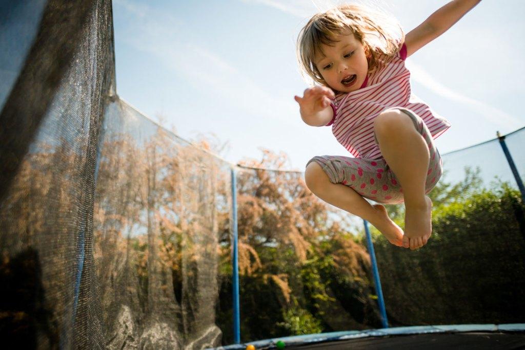 little girl bouncing on trampoline