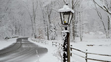 road covered in snow with a lamp