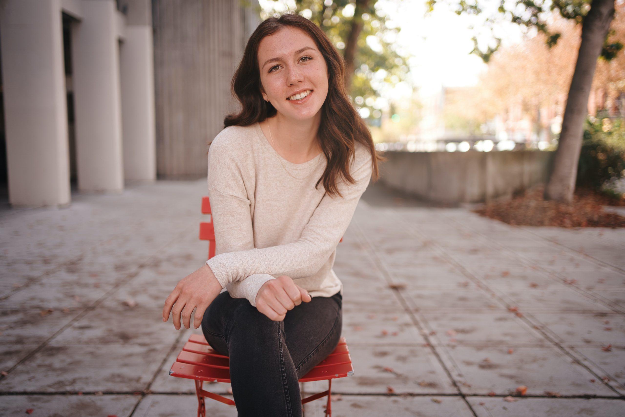 Highschool senior girl in white sweater sitting on sidewalk on bright red chair