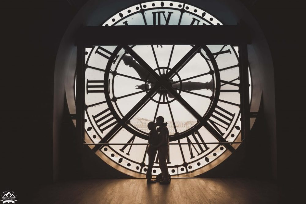 Shillouette of AJ and his wife in front of the clock inside the Musee d'Orsay