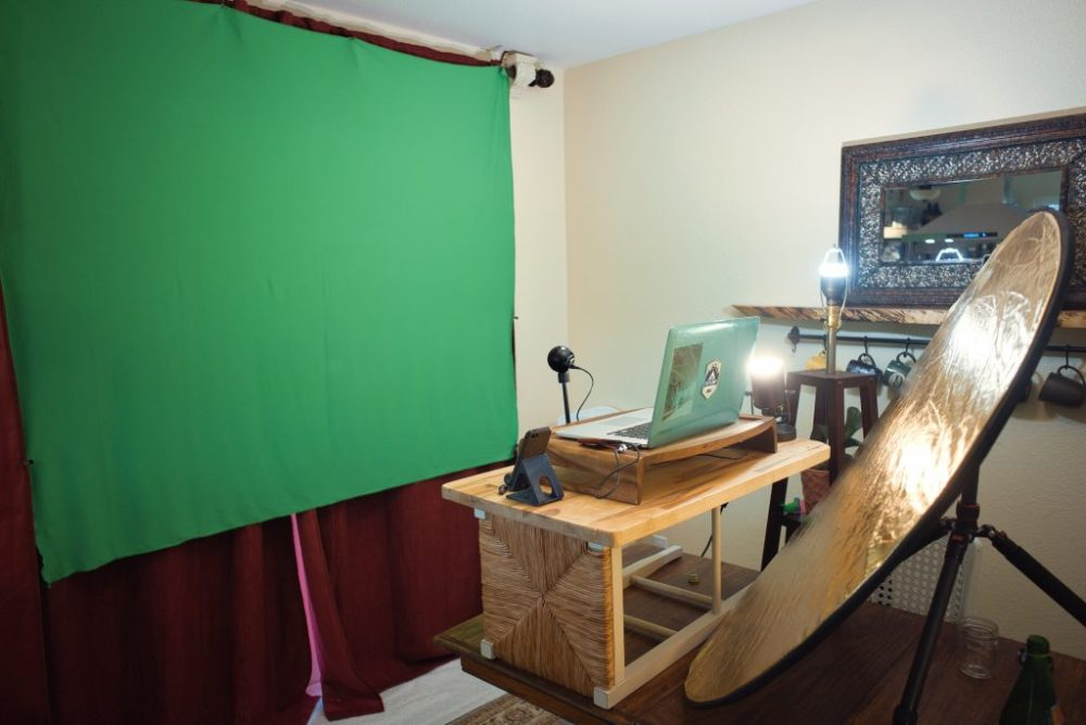 greenscreeen, reflector, macbook on a wood stand made of a sidways wooden square barstool and microphone. AJ's ad-hoc studio out of his dining room