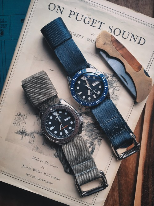 two seiko diver watches, one on an origional green ZA strap and the other on a grey ZA strap on the book On Puget Sound with a pocket knife