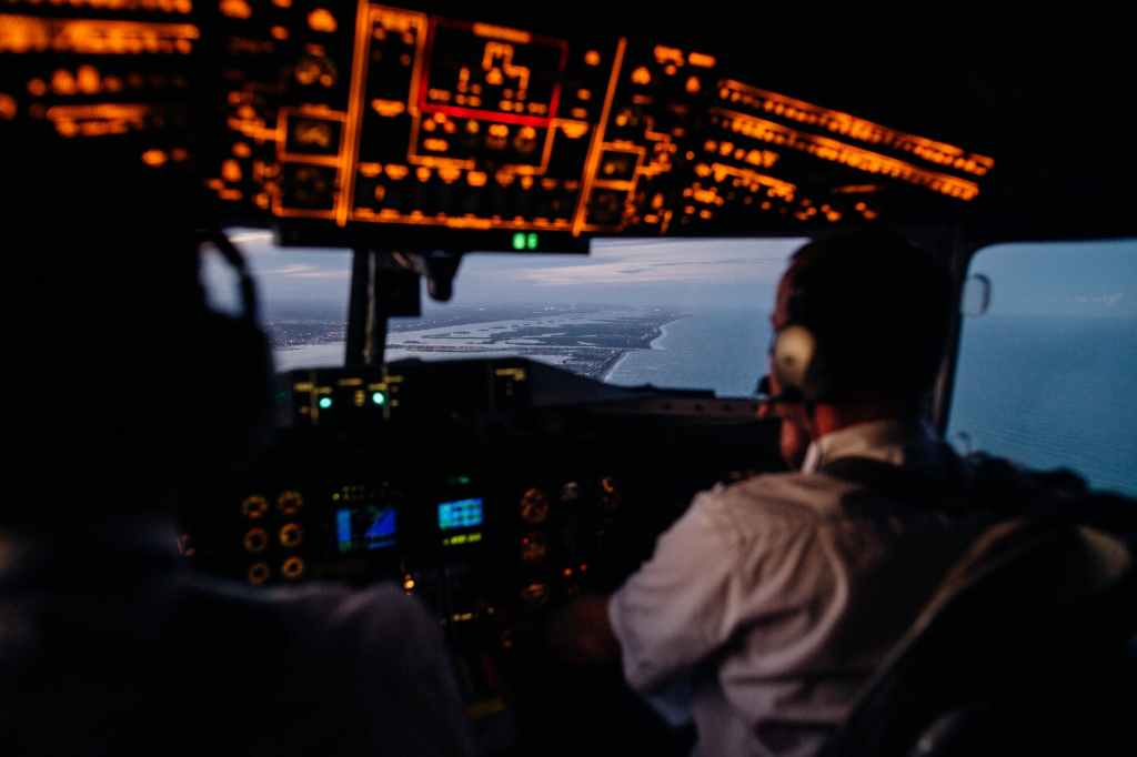 anonymous pilots in aircraft cockpit flying over sea