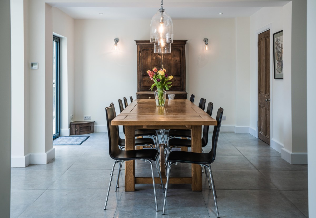 Central dining table with flowers and low hanging ceiling lights. A house extension built by AJ Hammond Builders in Bexhill East Sussex