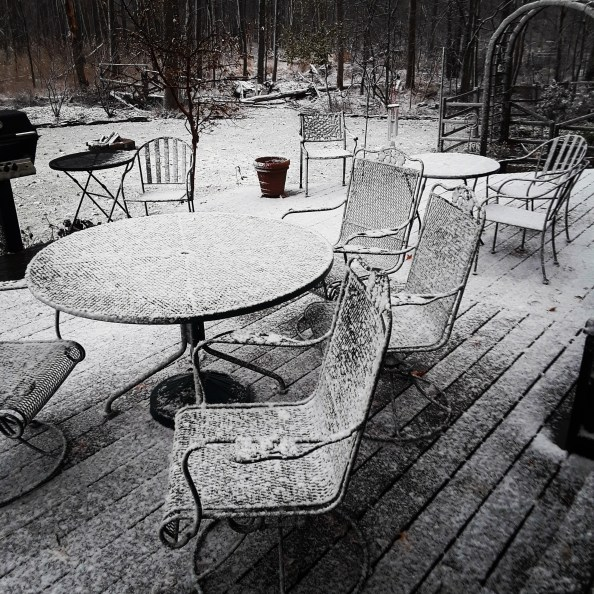 snow lightly covers patio furniture and wooden deck after the first snowfall of the season
