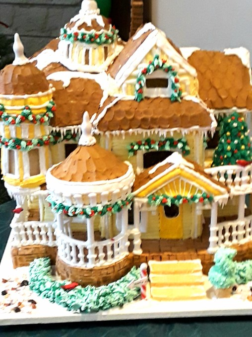 Victorian gingerbread house with yellow frosting and white trim icing