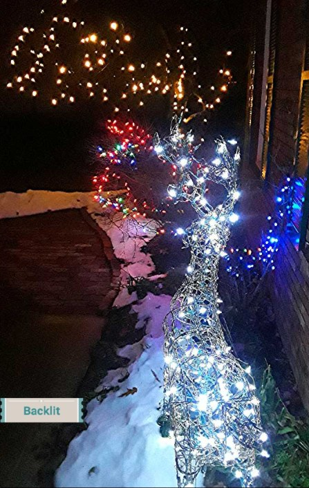 white lights on a grapevine deer, blue and multicolored lights on shrubs, and gold lights on crabtree