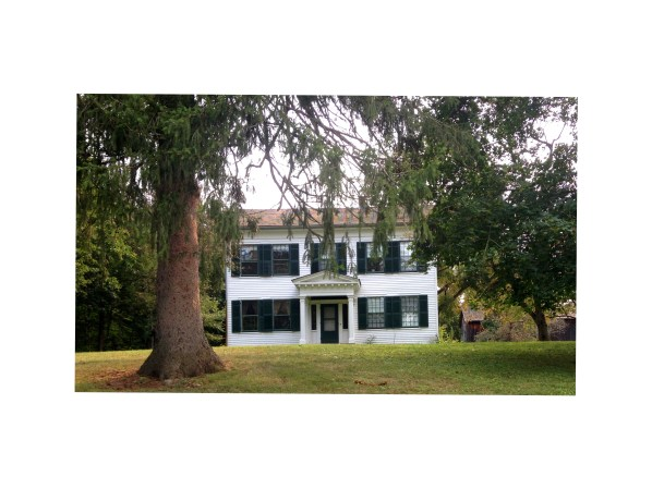 white clapboard farmhouse with dark green shutters