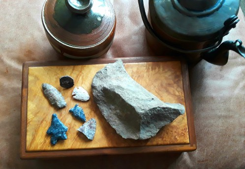 an assortment of arrowheads and a stone scraper