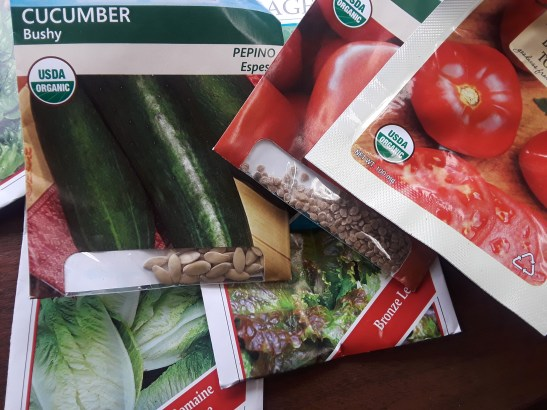 seed packets of tomatoes, cucumber, and lettuce