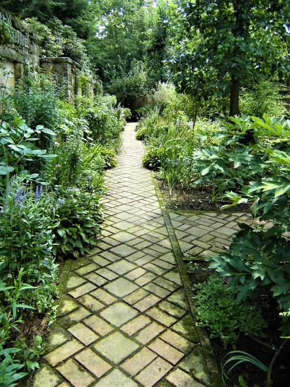 A brick path, set on the diagonal. leads through leafy green plant borders