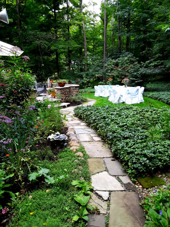 garden flowers flank both sides of the bluestone path, white clothed tables show in the distance