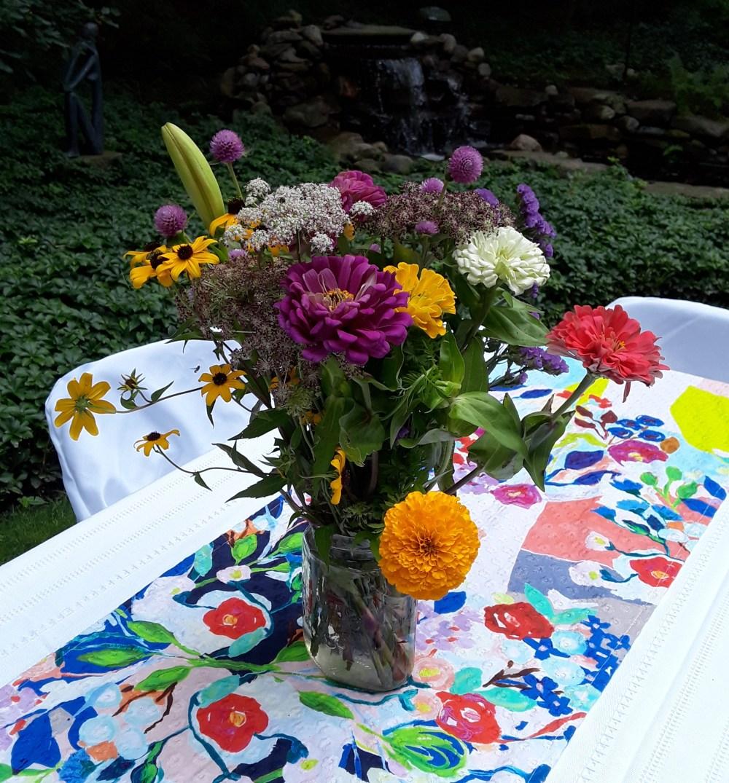 zinnia, marigold, rudbeckia, lilies in mason jars decorating tables