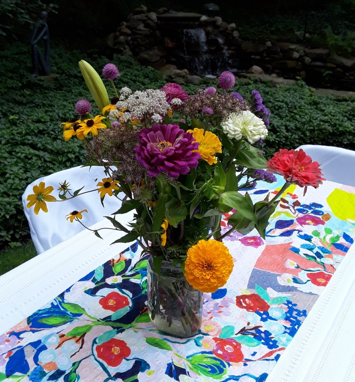 zinnia, marigold, rudbeckia, lilies in mason jars decorating tables