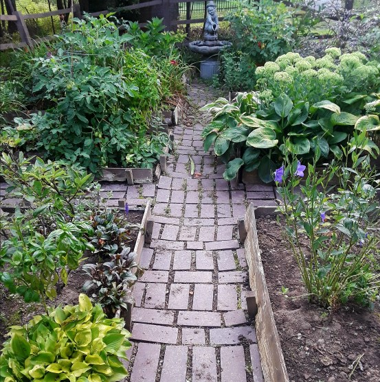 fenced garden with brick paths and raised beds