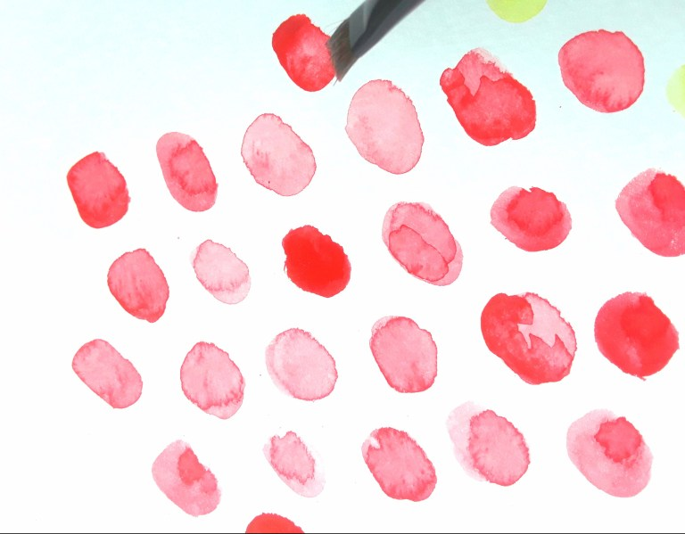 watercolors are used to repeat a red dot pattern on paper