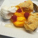 A slice of peach galette topped with raspberries and ice cream