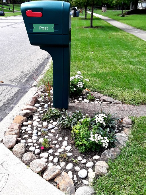 mailbox garden is mulched with river stone