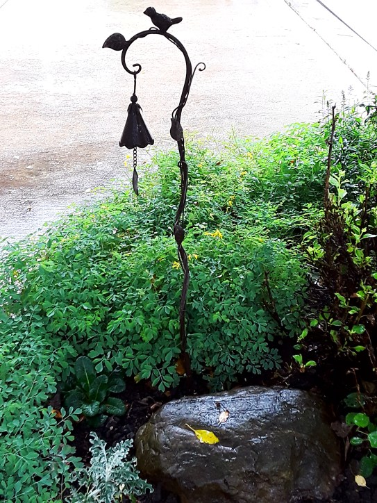 a metalwork bell hangs over a flower border