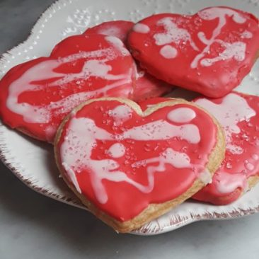 A white porcelain plate holds pink frosted heart shaped sugar cookies