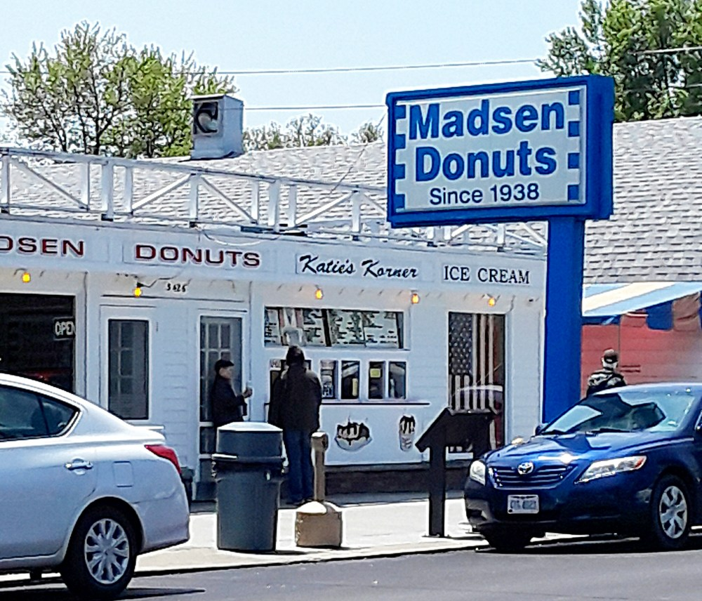 "Little white storefront of doughnut shop, with blue and white sign ""Madsen Donuts Since 1938."""