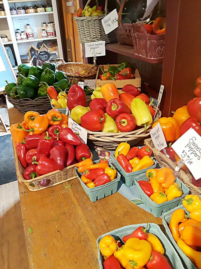 Yellow, red, orange, and green peppers displayed in baskets.