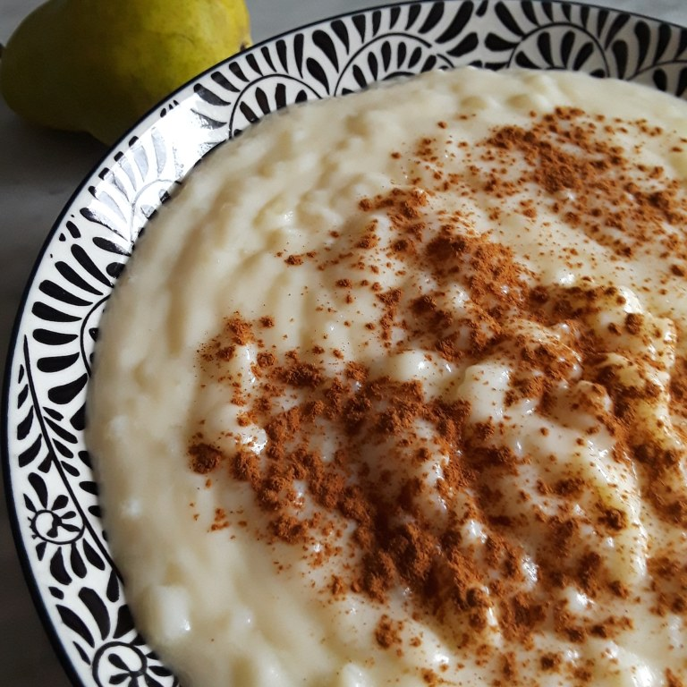rice pudding in a large serving bowl is sprinkled with cinnamon