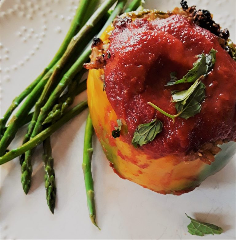 Middle Eastern Style Stuffed Peppers are capped wih tomato puree and a sprinkling of chopped mint leaves.