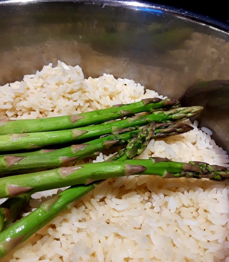 asparagus spears are spread out on top of cooked rice in the rice pot