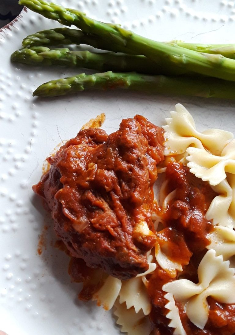 Greek chicken is served with fresh asparagus spears and bow-tie noodles