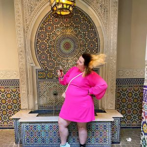 Heading picture for Promises of 2020 post. It features Chelsea in a bright pink dress, standing in front of a fountain, holding a glass of champagne, swinging her hair over her shoulder.