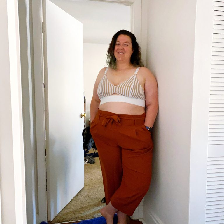 Image of Chelsea in a bra she made, with rust colored pants on.
