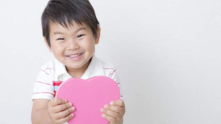 Congenital heart disease: little boy holding pink cardboard heart