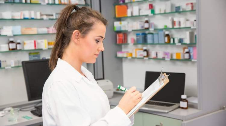 NAPSA student survey: young pharmacist writing on clipboard