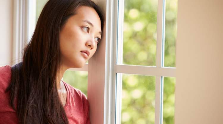 domestic violence concept, worried woman gazes out of window