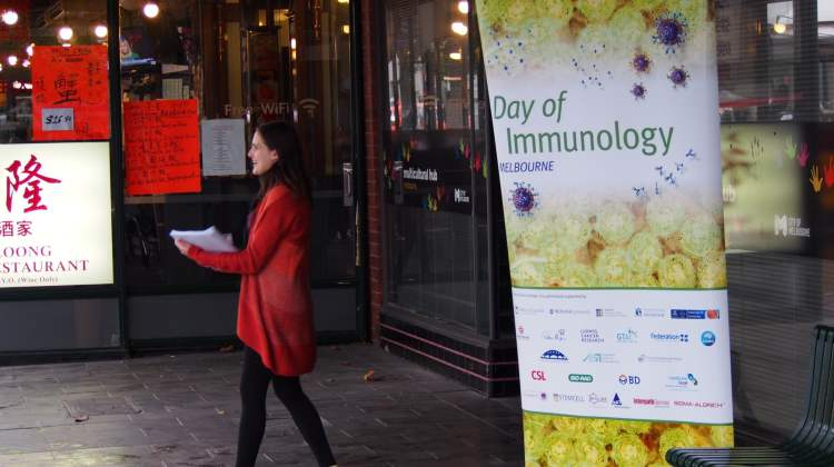 woman in red coat walks past the Vaccination Café sign