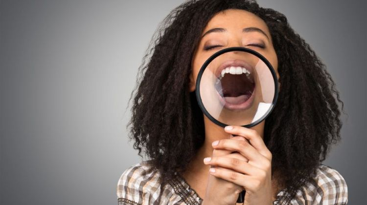 "dental and oral problems: woman says ""aah"" into magnifying glass to show white teeth"