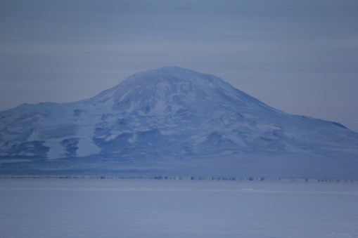 View of Mt. Discovery across the sound from McMurdo station. The thick band that you see at the base of the mountain, which looks like a tall cliff, is not actually there. This is a Fata Morgana mirage (see the next image). © A. Padilla