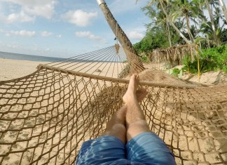 holiday maker relaxing on hammock at beach
