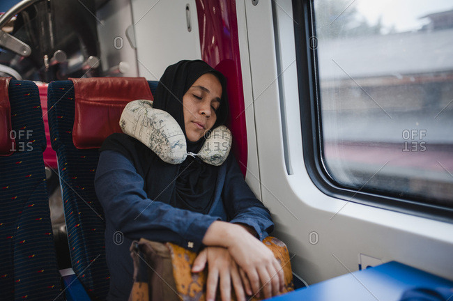 woman using a travel pillow sleeping on